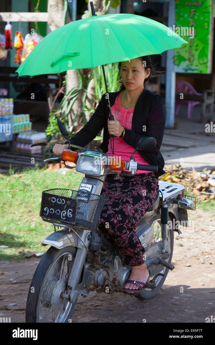 A woman uses one hand to ride her motor-cycle and uses the other to hold an umbrella, shading her from the sun. - Stock Image