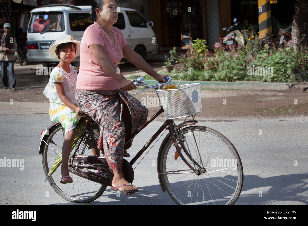 A woman (mother) rides her pedal cycle on a street in Hsipaw, Burma, a girl (her daughter) rides behind and looks - Stock Image