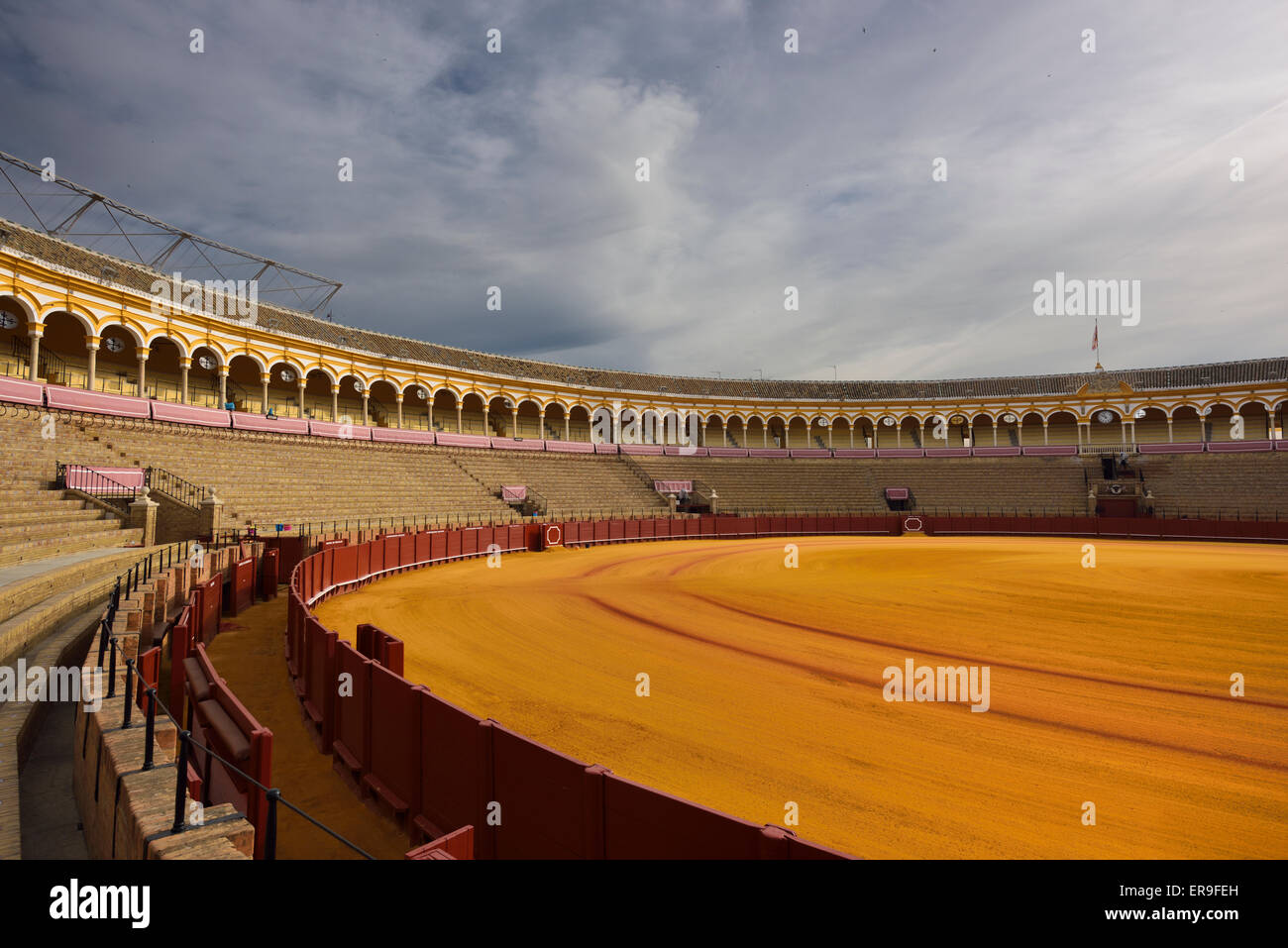 Golden sand and empty stands at Seville bullfighting ring - Stock Image