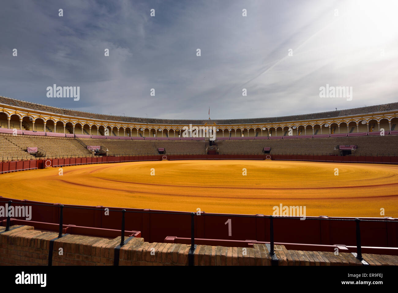 Golden groomed sand and empty stands at the Seville bullfighting ring - Stock Image