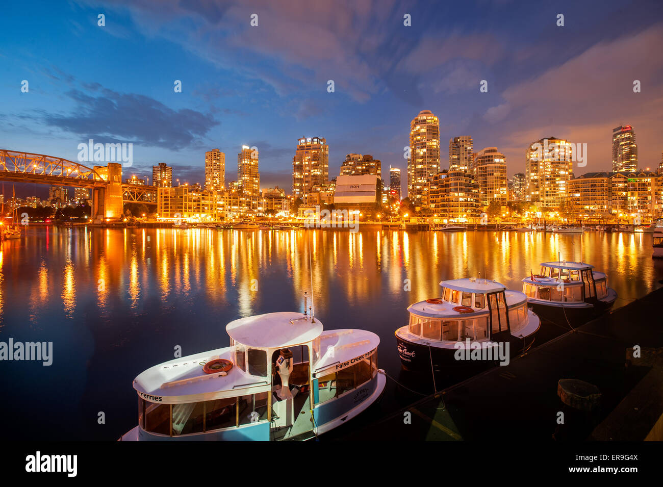 Vancouver Yaletown skyline and False Creek at dusk, as seen from Granville Island.  Vancouver ferry boats at sunset - Stock Image