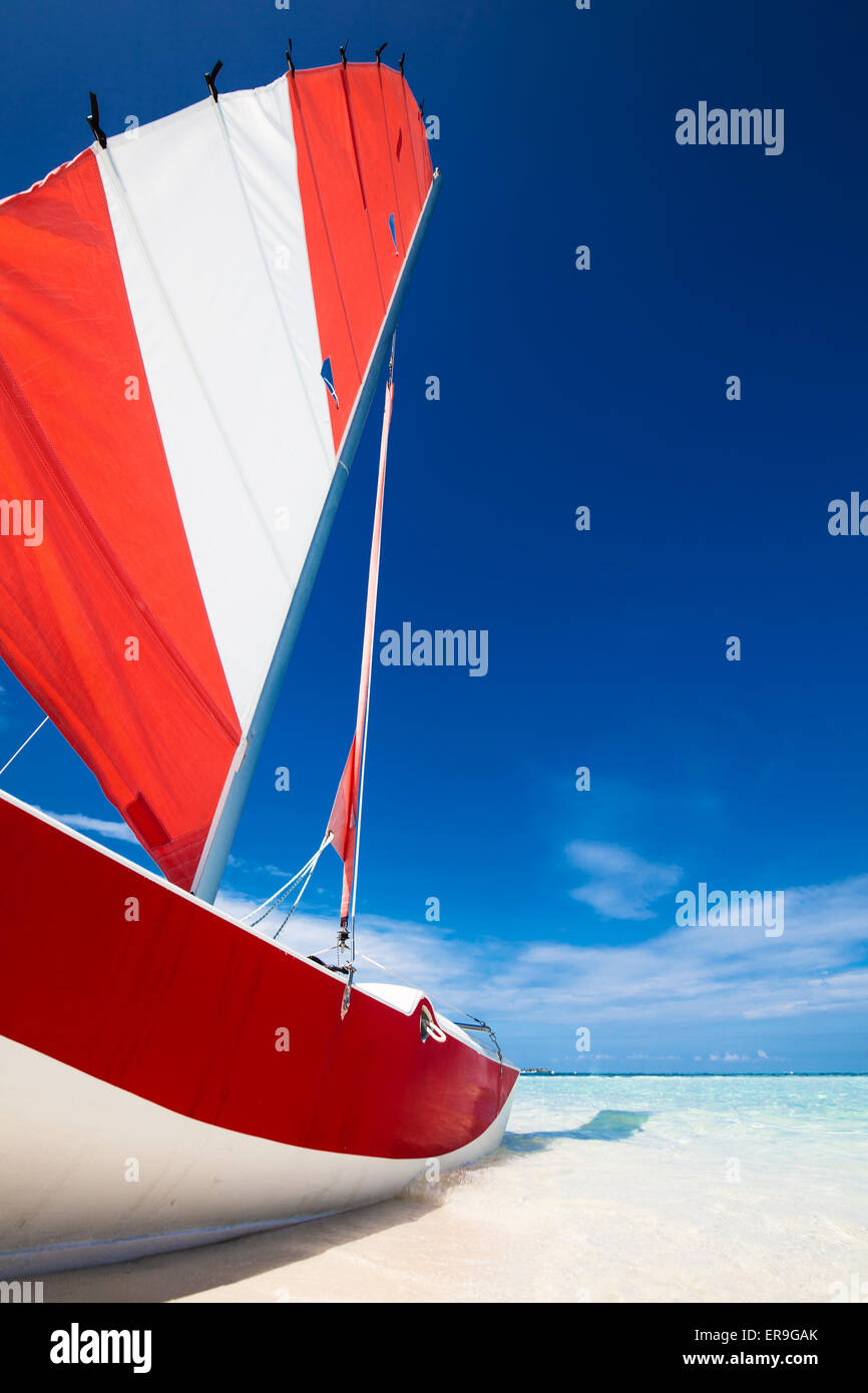 Sailing boat with red sail on a beach of deserted tropical island with shallow blue water - Stock Image
