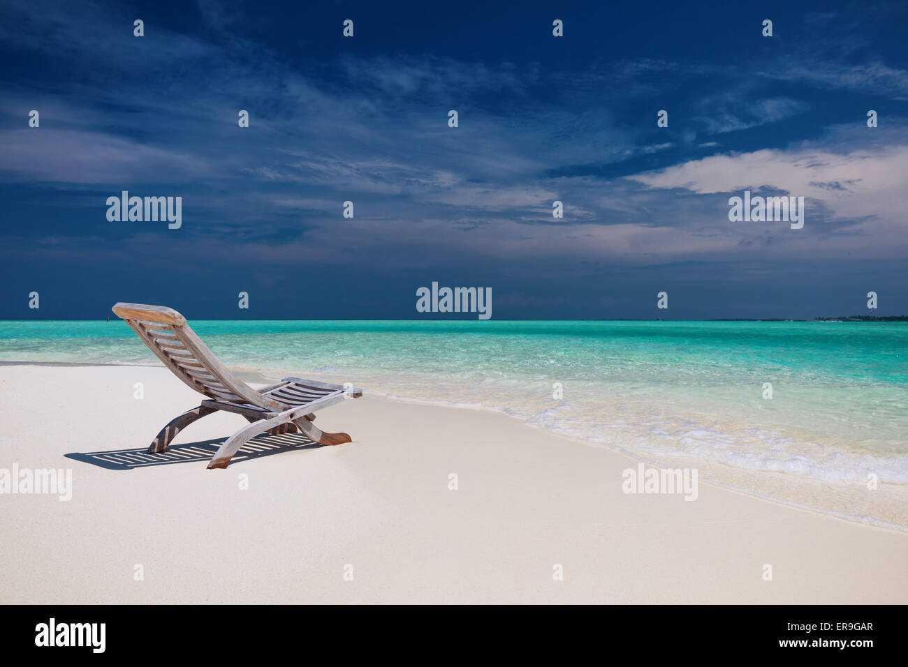 Beach view of amazing water in Maldives - empty chair on sand - Stock Image