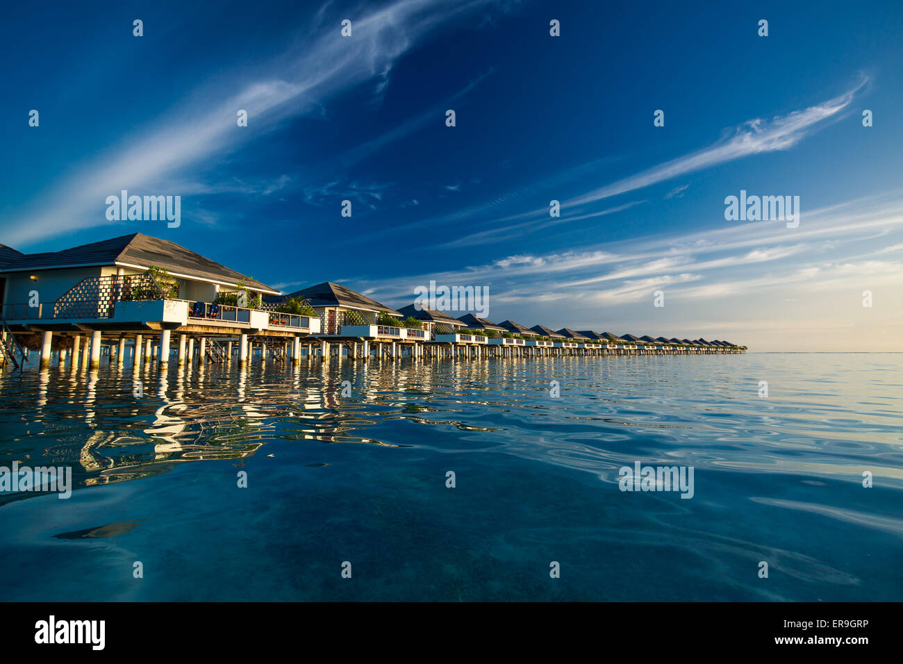 Over water villas in Maldives reflected in blue lagoon before sunset - Stock Image