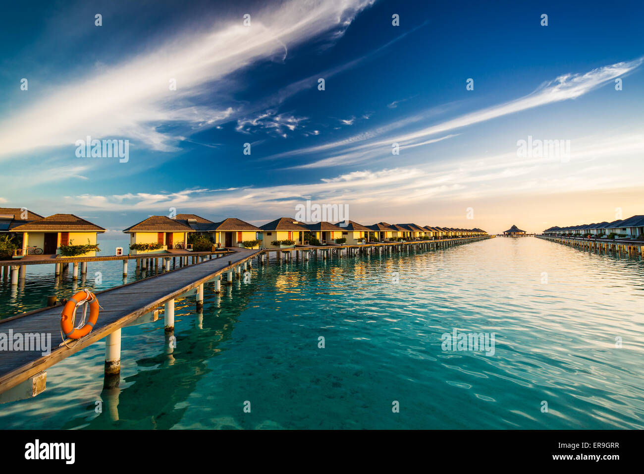 Sunset time on island of Maldives over the bridge connecting over-water bungallows - Stock Image
