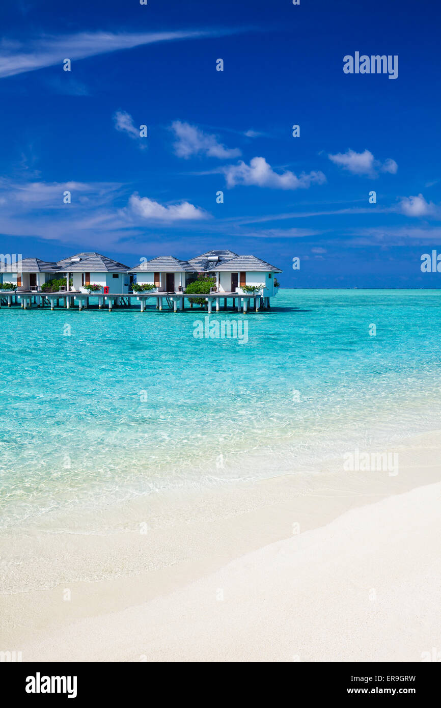 Water villas in the tropical ocean and white sandy beach - Stock Image