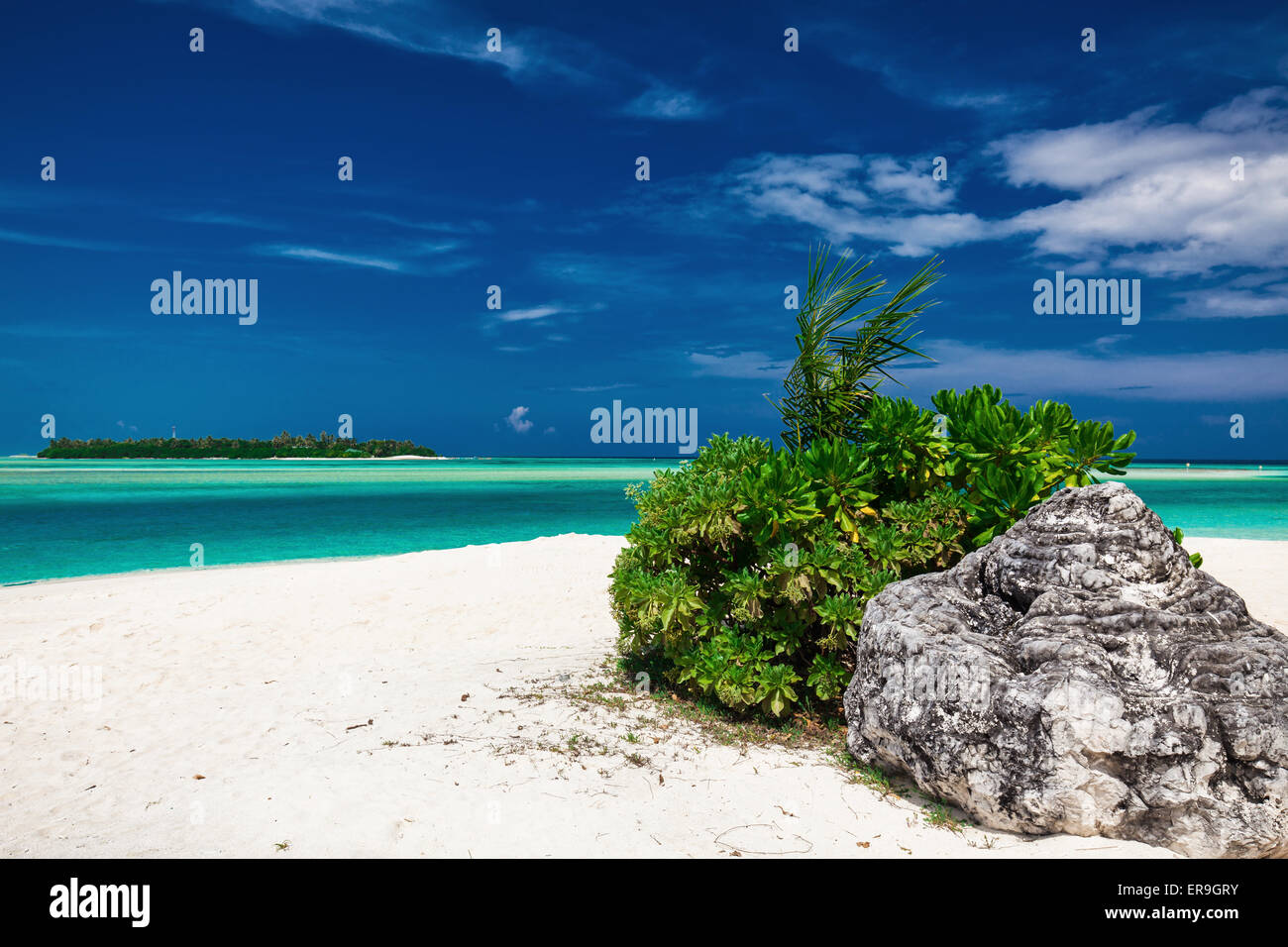 Dreamy crystal clear sea with a rock on the white sandy beach - Stock Image