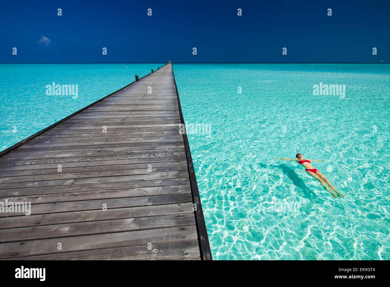 Young woman in red bikini swimming next to jetty in azure water of Maldives - Stock Image