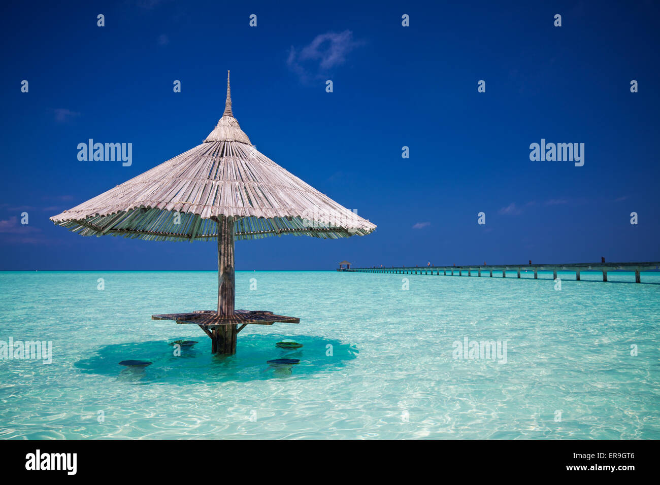 Bamboo beach umbrella with bar seats in the water at Maldives - Stock Image