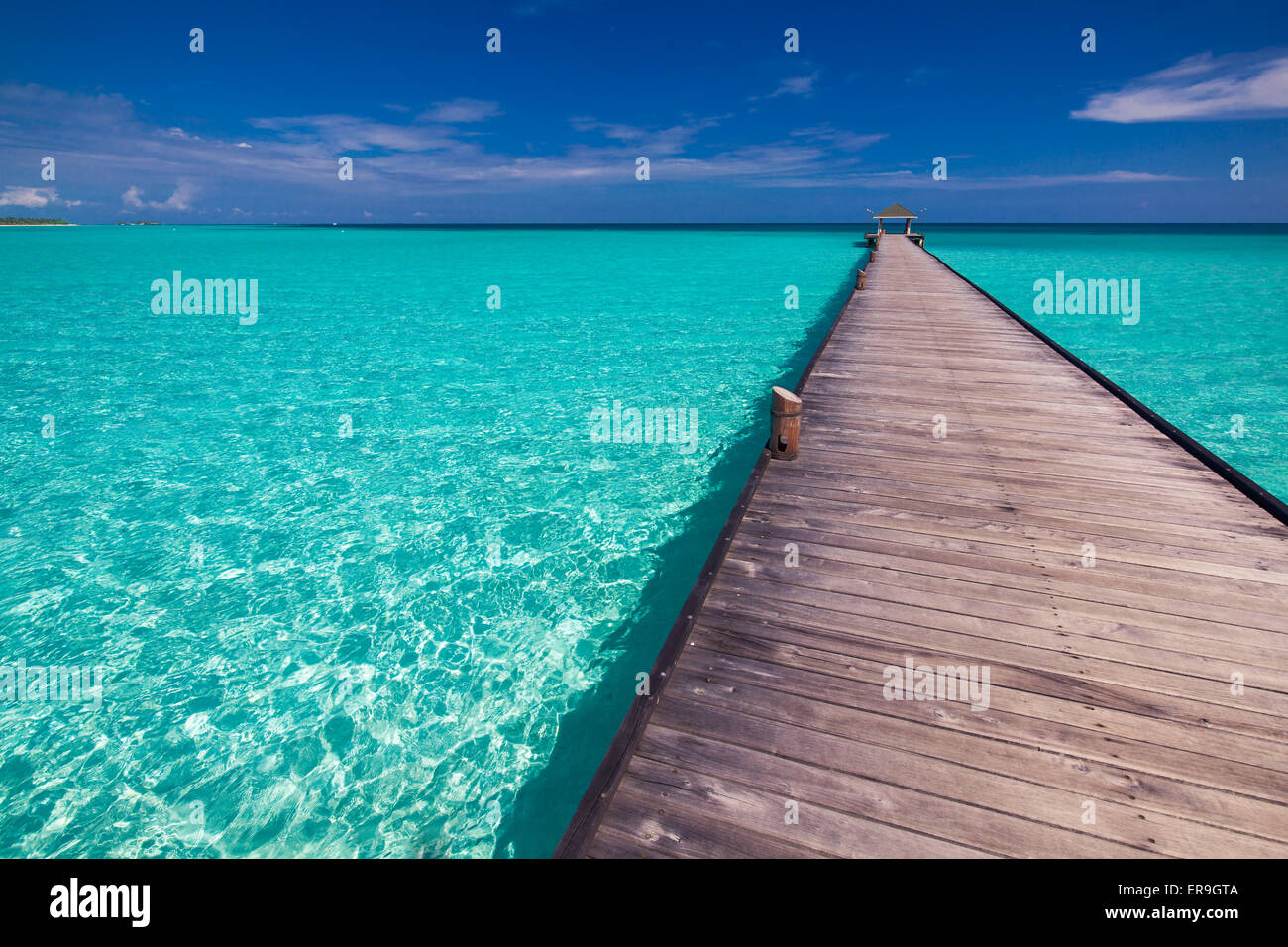 Wooden long jetty over lagoon in Maldives with amazing clean water Stock Photo