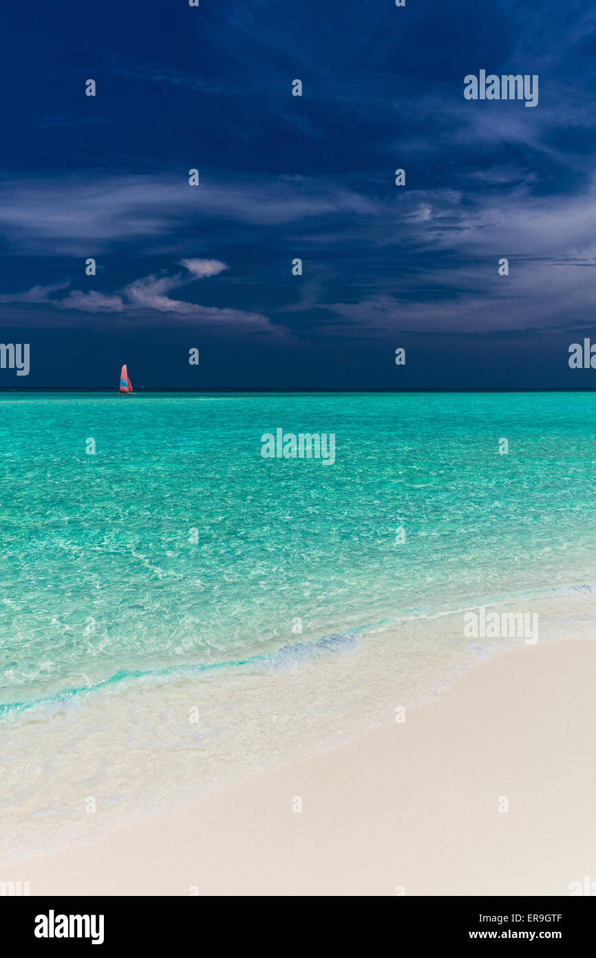Paradise beach in Maldives with single red sail boat in the ocean - Stock Image