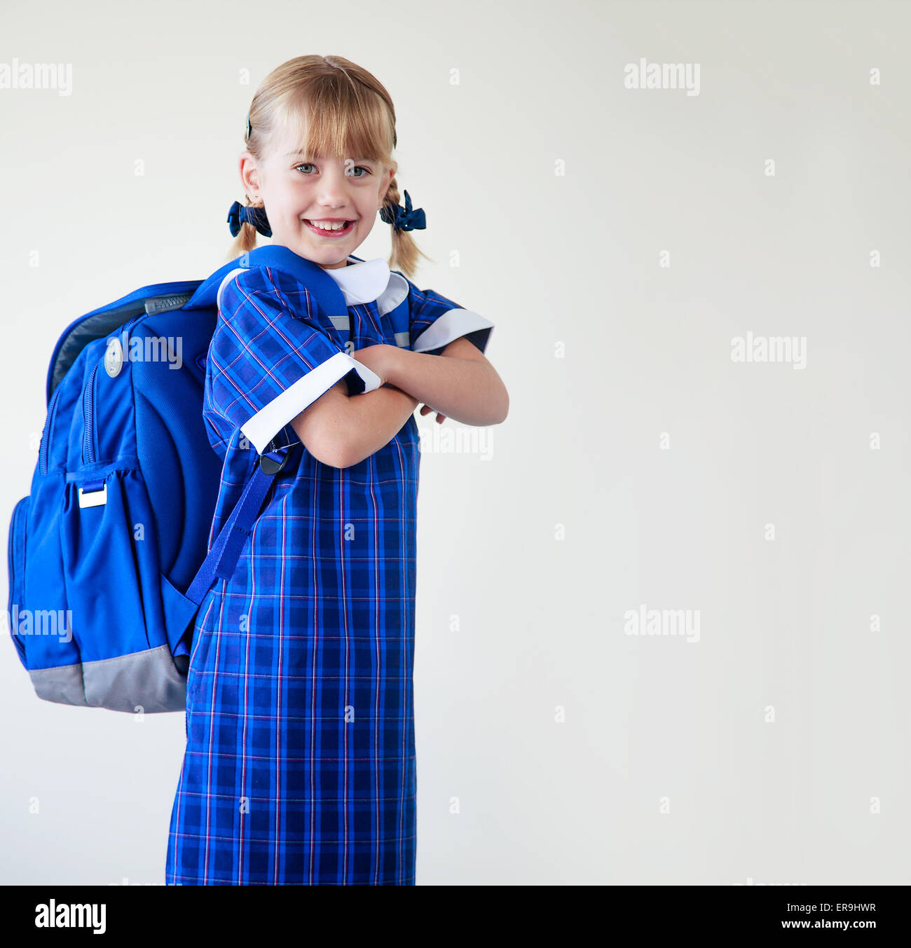Little girl dressed in her school uniform and backpack ready to go to school - Stock Image