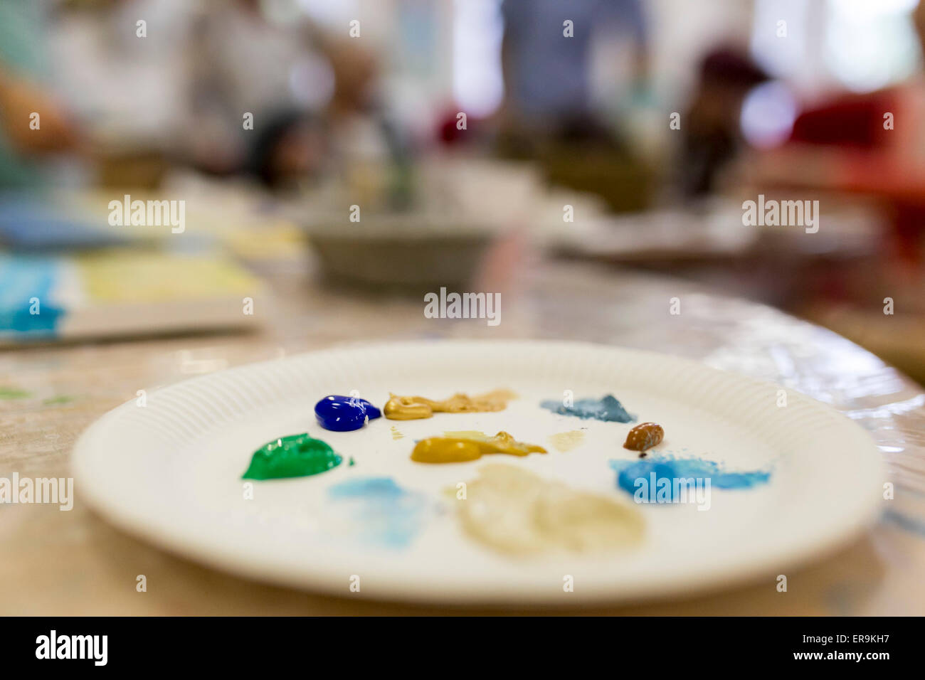 a paper plate being used as a paint palette - Stock Image