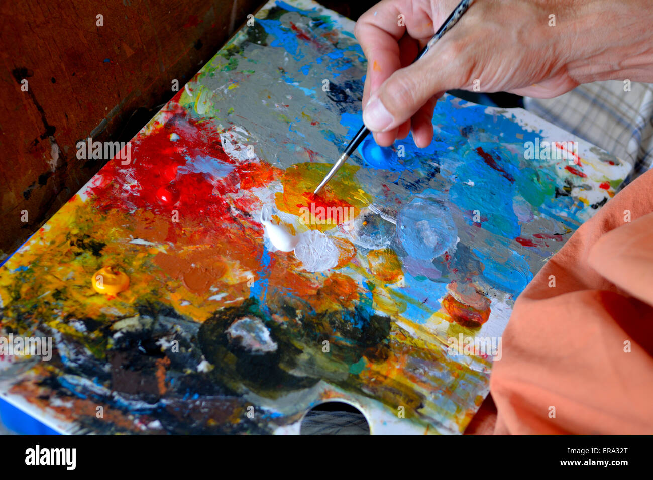 Artists paint pallet board with colourful oil paints - Stock Image
