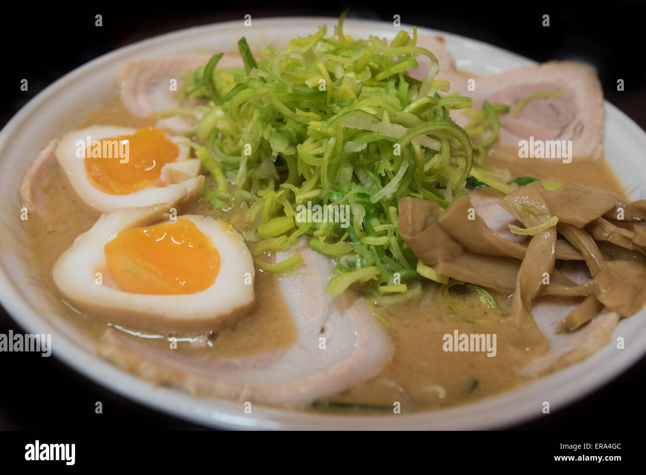 Closeup of a ramen  noodle soup with porc, chives, eggs, bamboo and leek isolated on black background Stock Photo