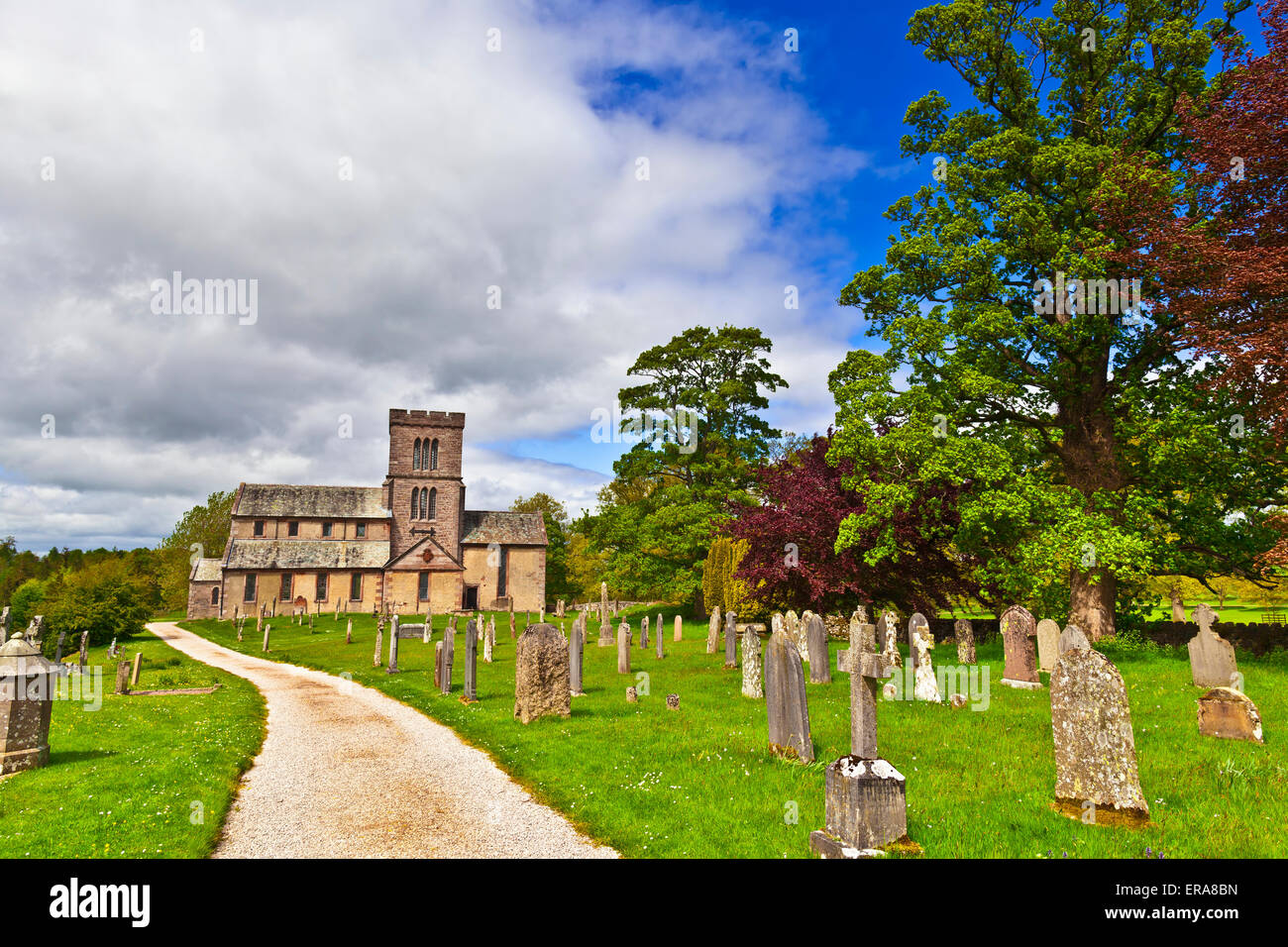 Countryside view with old road through graveyard to a rural English church. - Stock Image