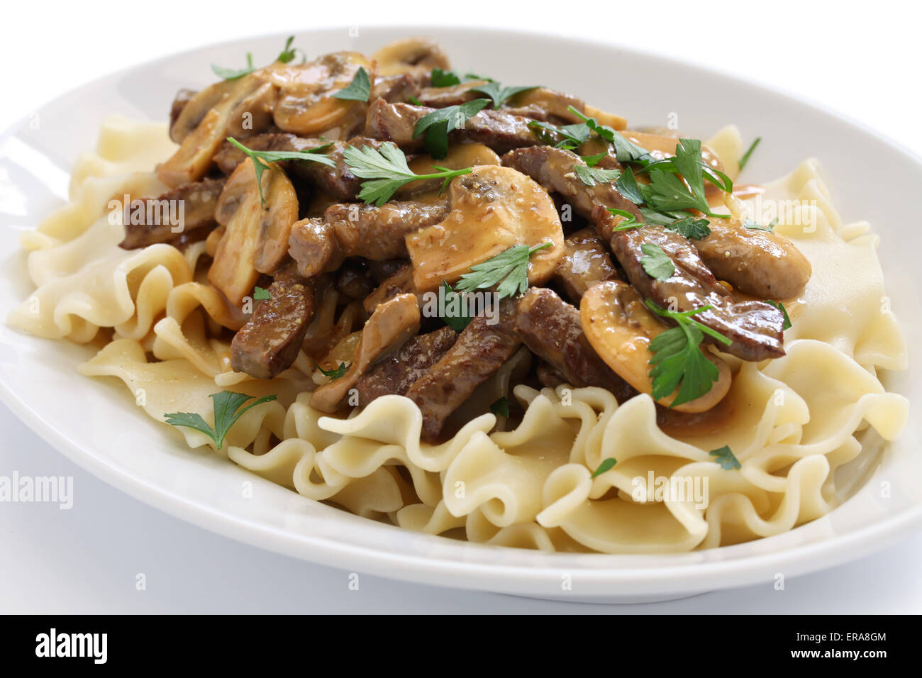 beef stroganoff with pasta, russian cuisine isolated on white background - Stock Image