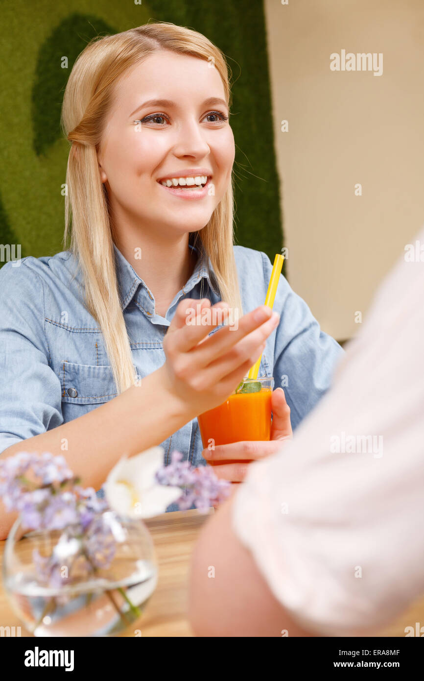 Smiling girl with cocktail in cafe. - Stock Image