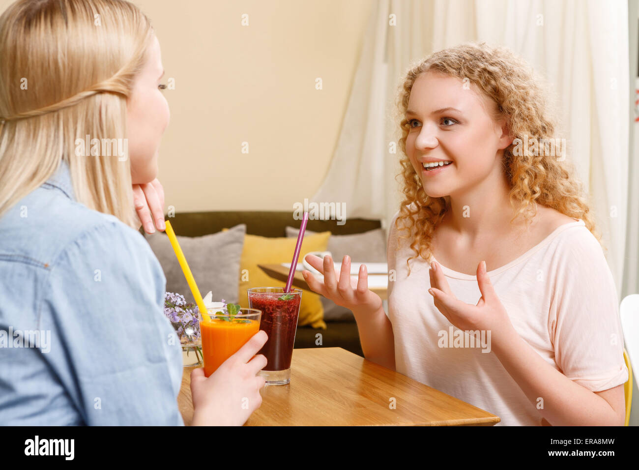 Two girls having conversation in cafe - Stock Image