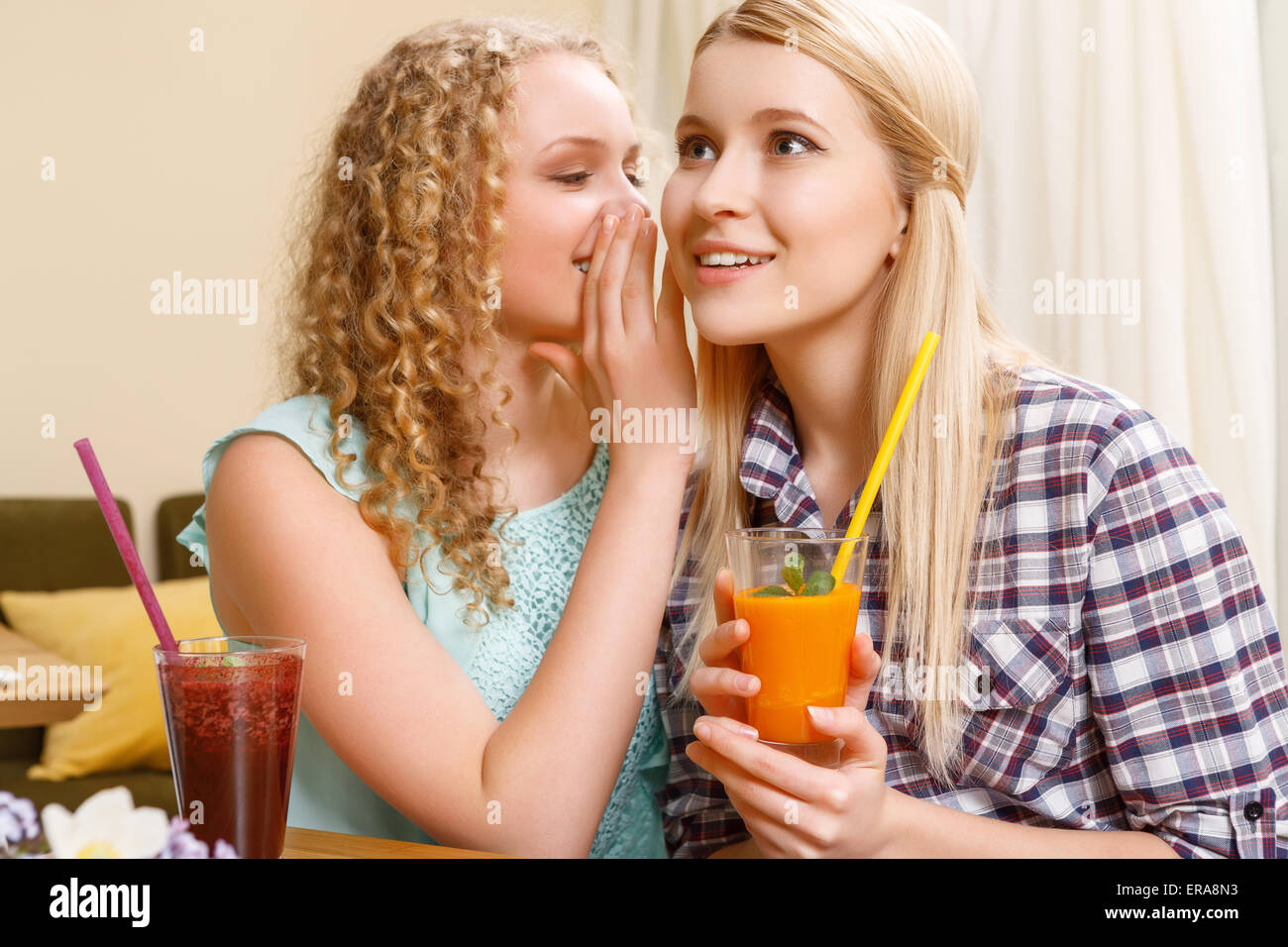 Girl telling secrets to her friend in cafe - Stock Image