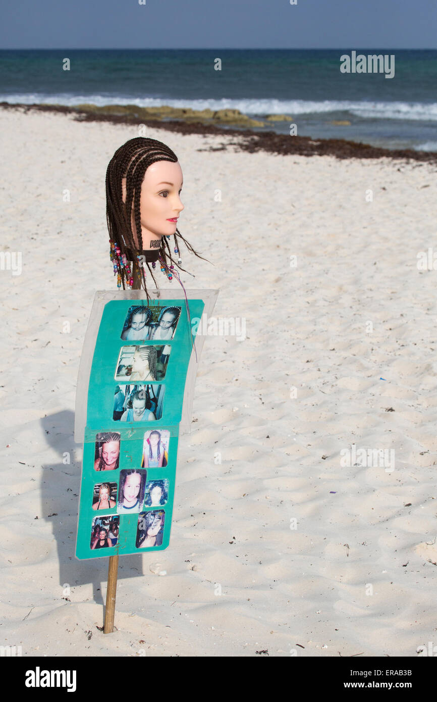 Mannequin head and photos advertising braiding on the beach - Stock Image