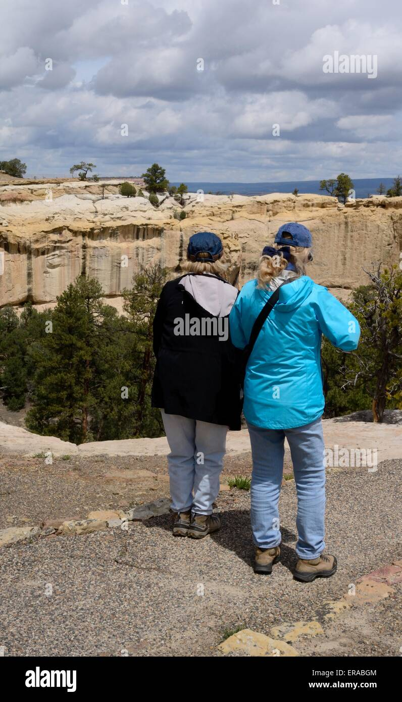 Friends overlooking valley from sandstone bluff at El Morro National Monument New Mexico - USA - Stock Image
