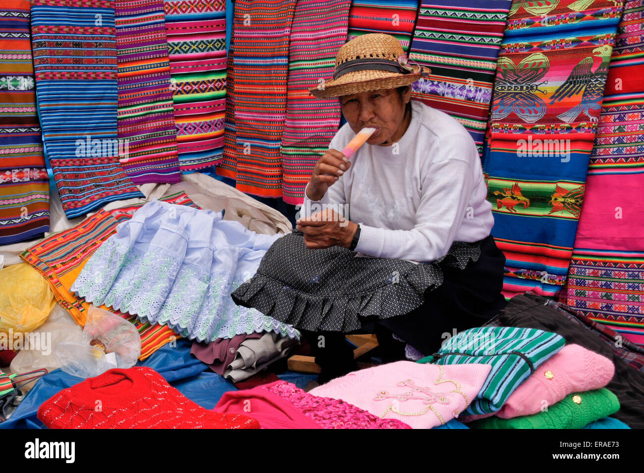 Woman selling clothing and textiles at Sunday market, Quiquijana (near Cuzco), Peru - Stock Image