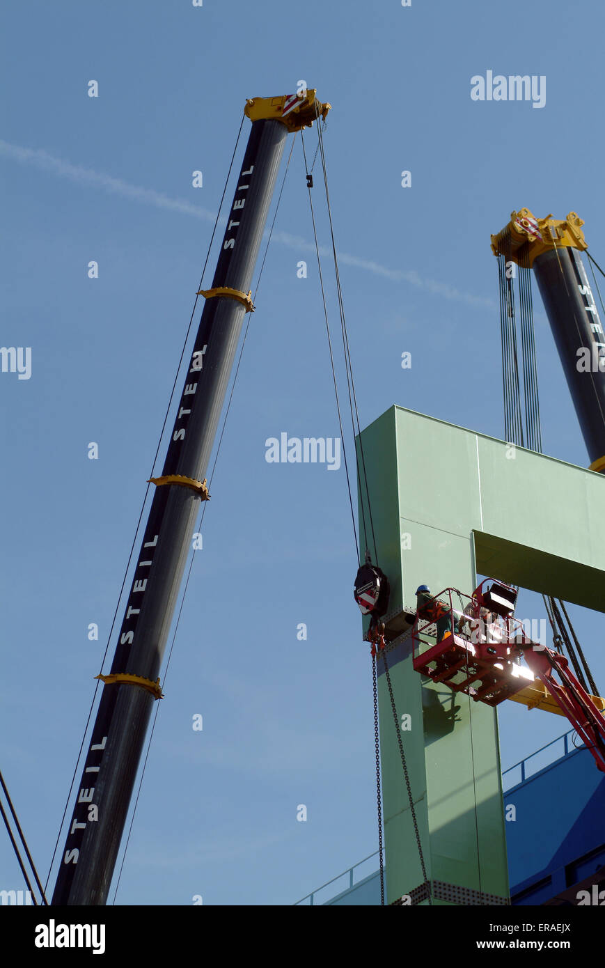 Two Worker installing a metal bridgehead in a harbor - Stock Image