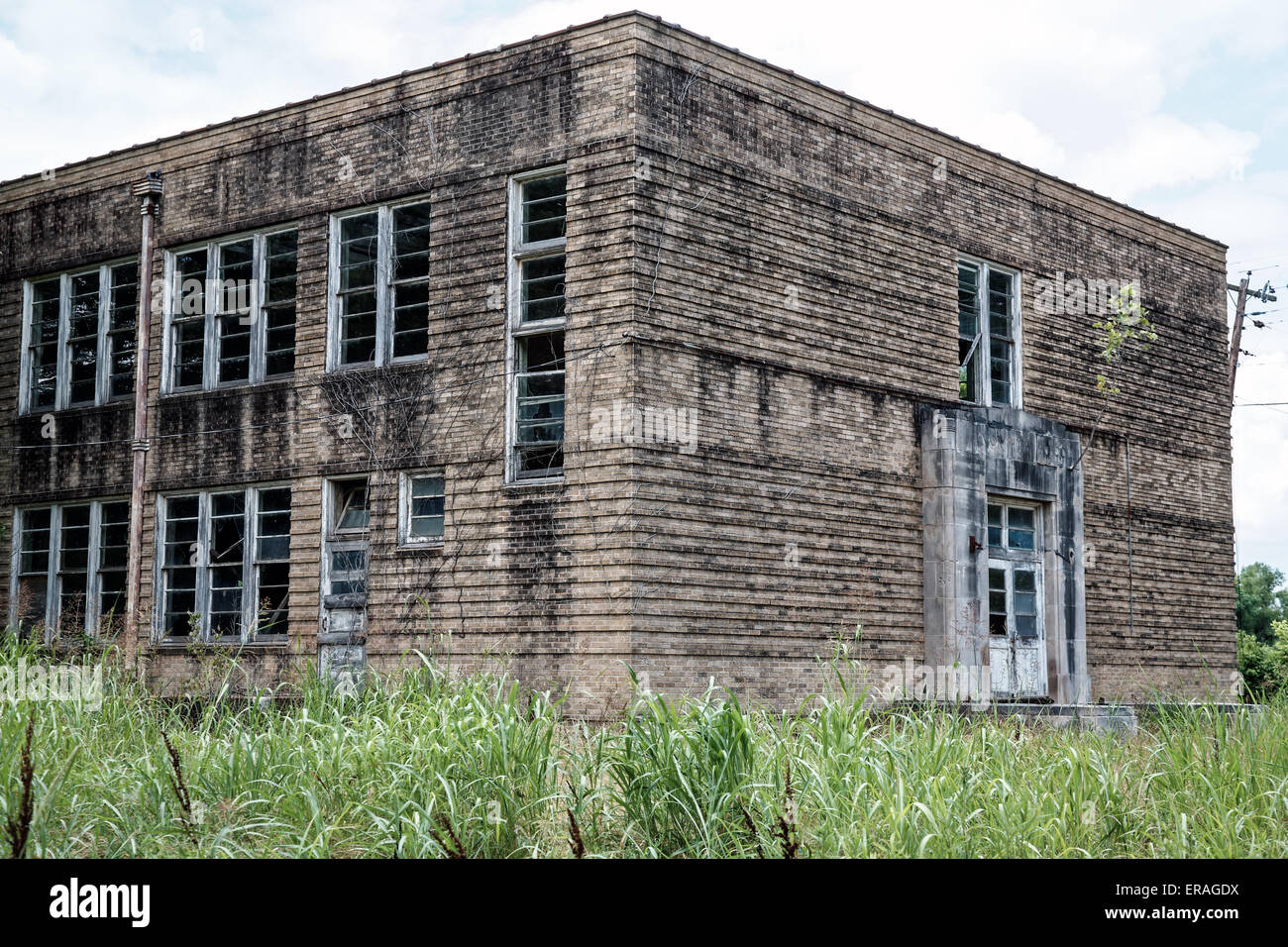 Abandoned junior high school in rural northern Lousiana.  Gray, dilapidated building surrounded by high weeds. - Stock Image