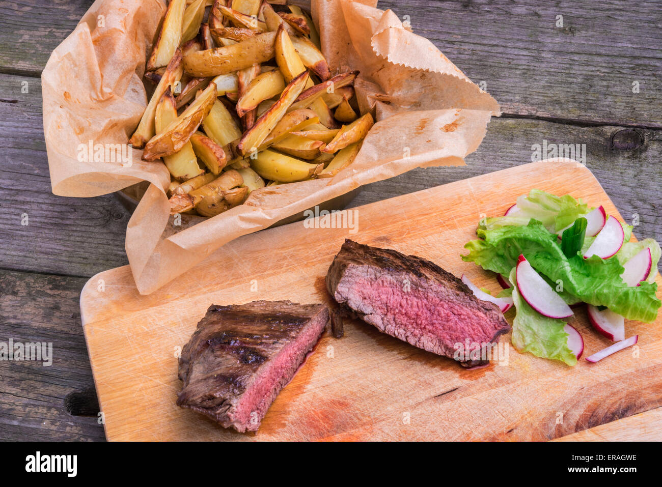 Medium rare grilled top rump steak seasoned with green pepper and thyme, served on a wooden board with rosemary Stock Photo