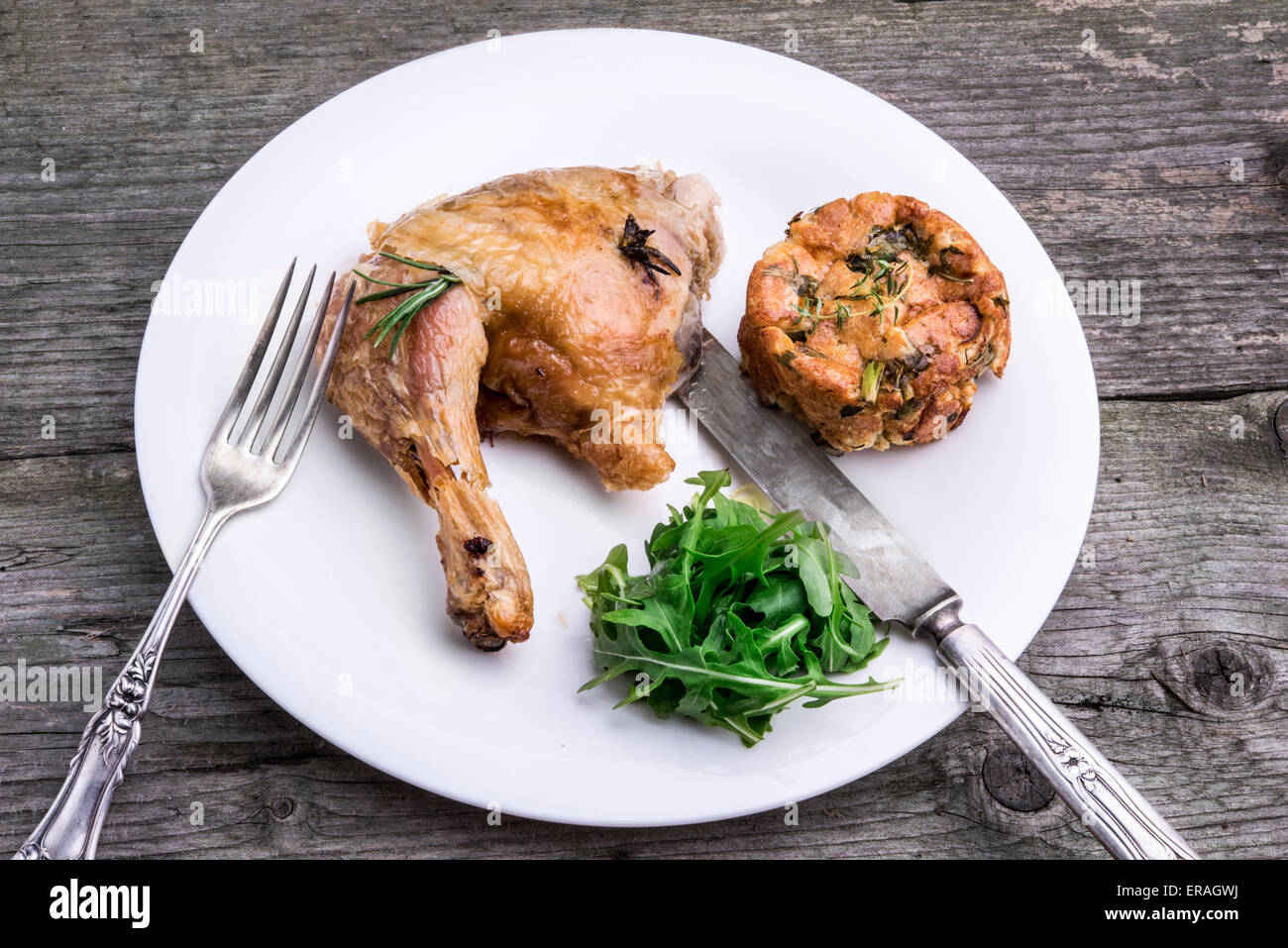 Roast chicken leg with rosemary and herb stuffing served with arugula salad and fresh herbs. - Stock Image