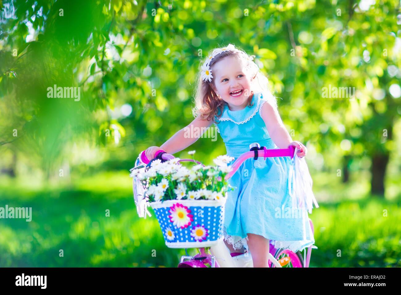 happy child riding a bike. cute kid biking outdoors. little girl in