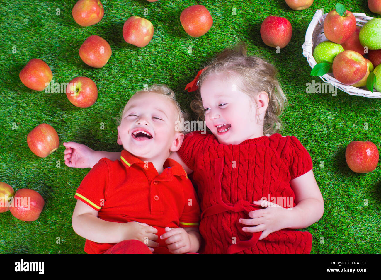 Child eating apple. Little girl and baby boy play peek a boo holding fresh ripe apples. Kids eat snack relaxing - Stock Image