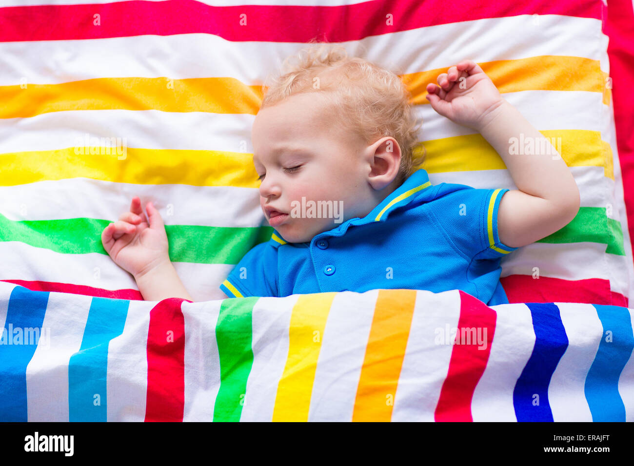 Child sleeping in colorful bed. Little baby boy asleep. Kids textile in rainbow color. Toddler kid relaxing on a - Stock Image