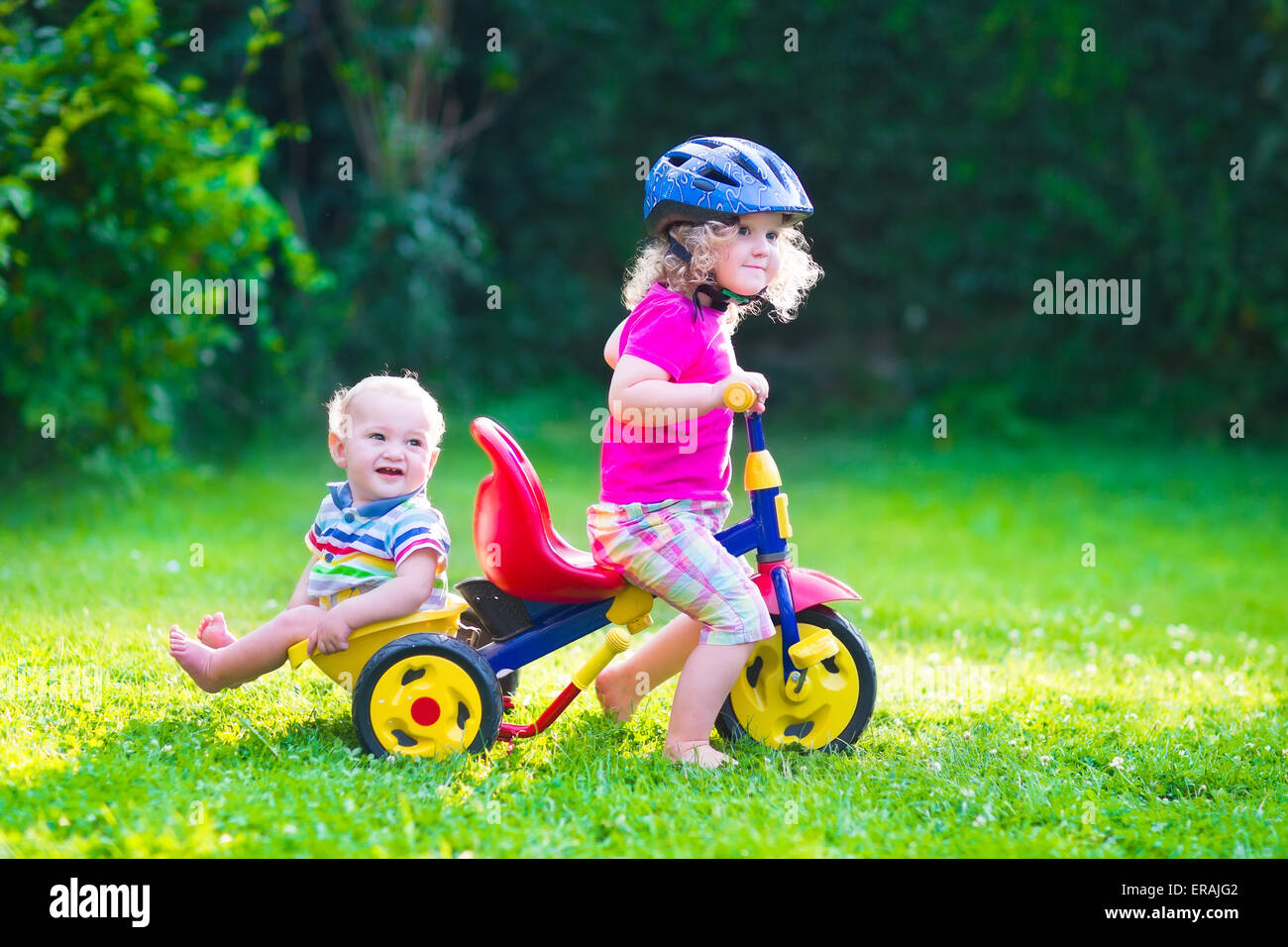 Children riding a bike. Kids enjoying a bicycle ride. Little preschooler girl and baby boy, brother and sister - Stock Image