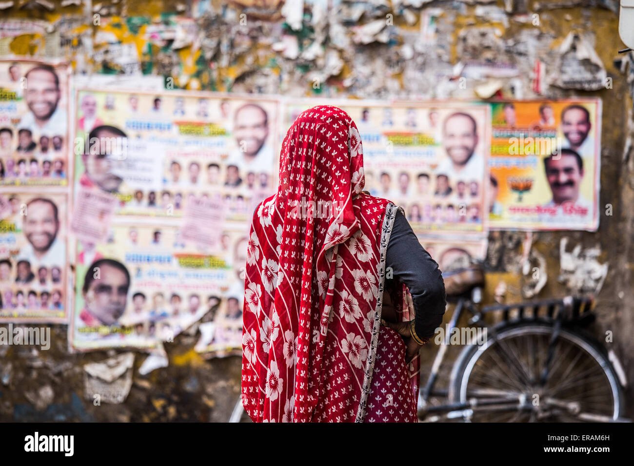 Indian woman standing in front of voting posters in Delhi, India - Stock Image