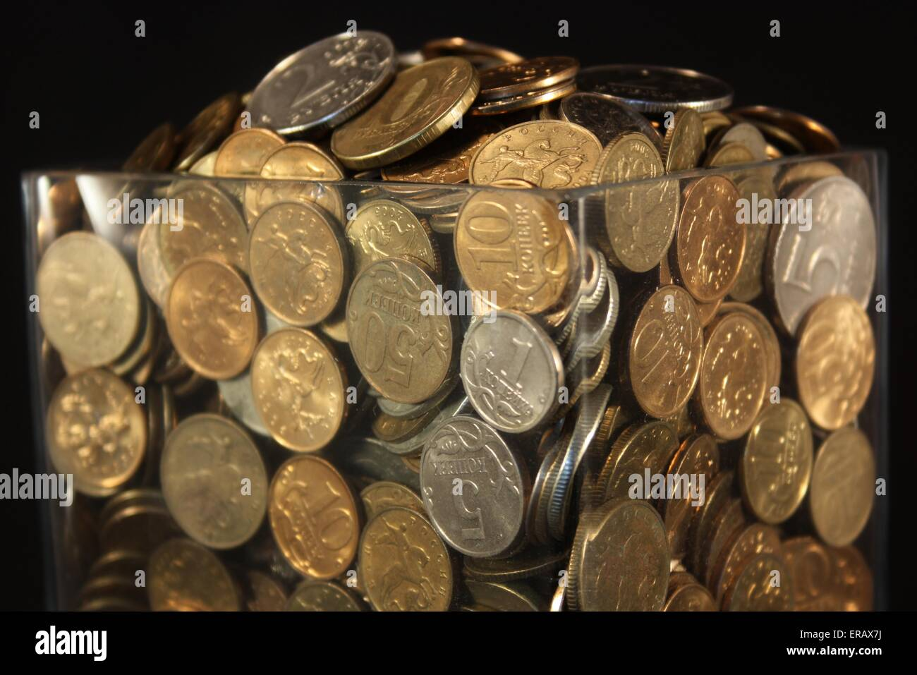 Coins in a glass jar on a black background - Stock Image
