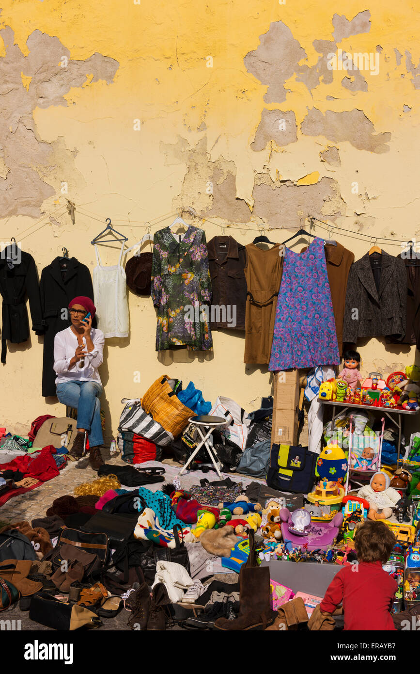 Woman on the phone surround by her wares for sale at Feira Da Ladra, or Thieves Market. - Stock Image
