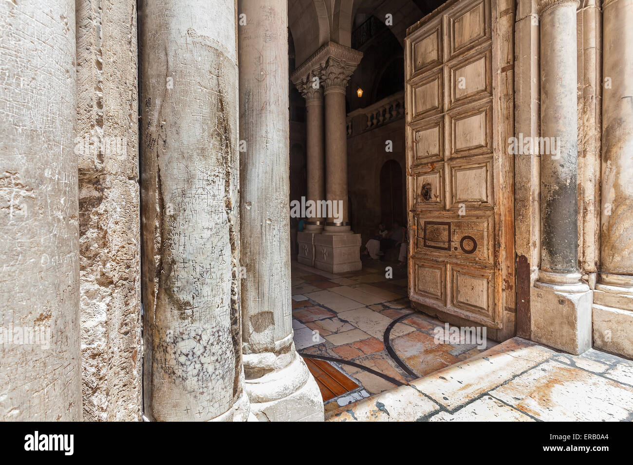 Marble pillars and old wooden door at the entrance to the Church of the Holy Sepulchre in Jerusalem, Israel. - Stock Image