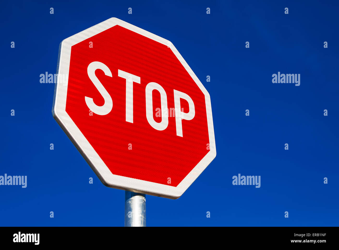 Stop Sign as Traffic Signalization over Blue Daylight Sky - Stock Image
