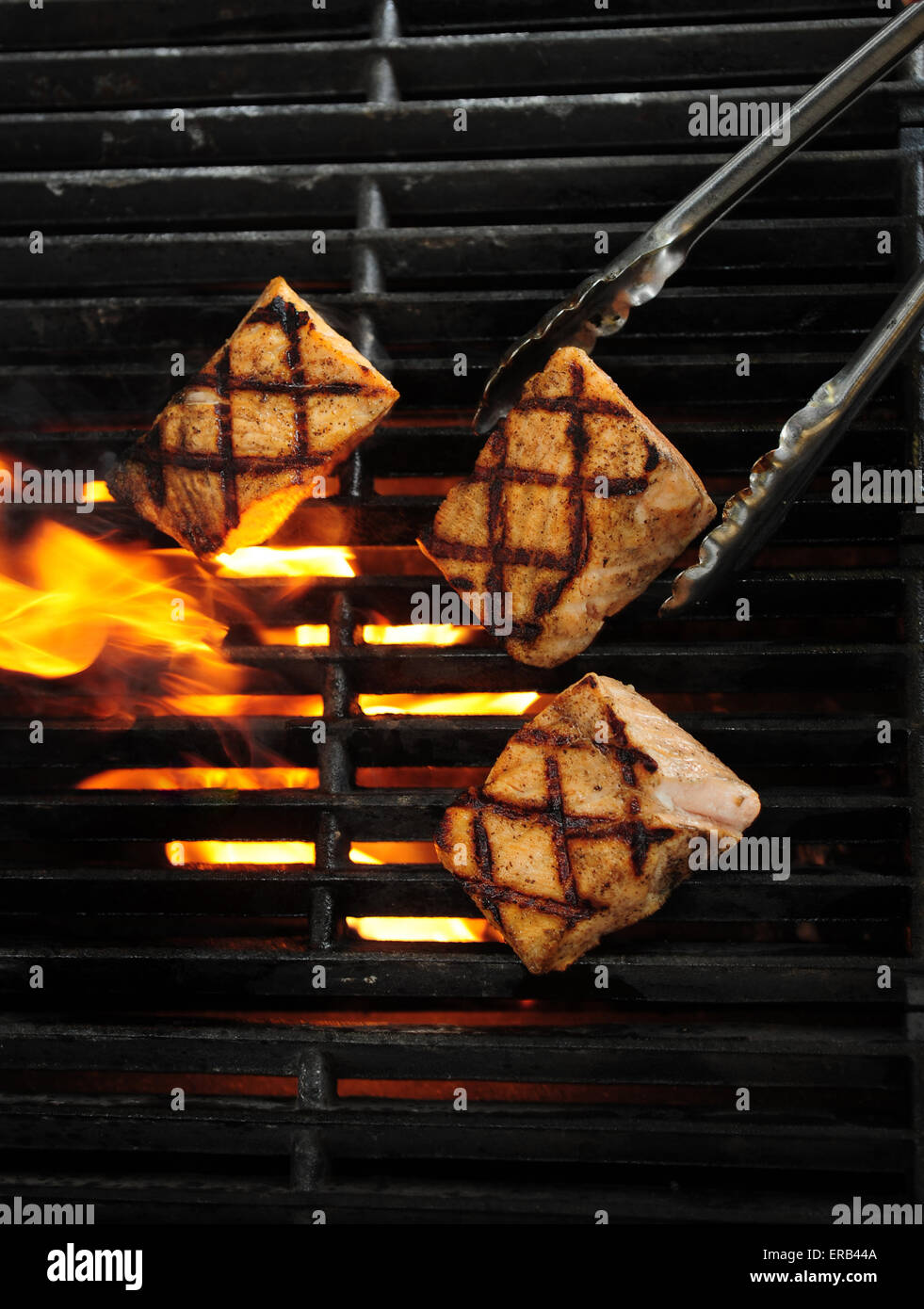 Metal tongs gripping pieces of salmon fish being grilled with an open flame - Stock Image