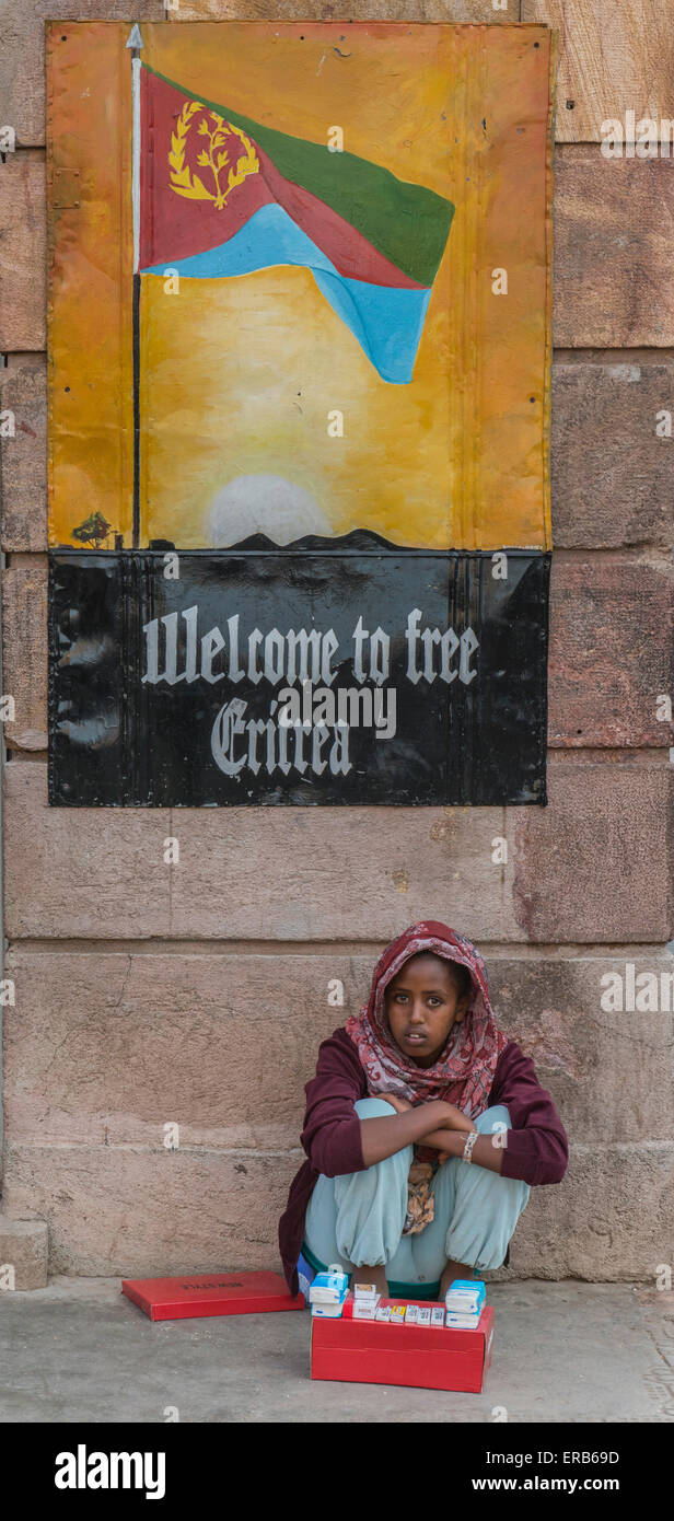 Woman Selling Cigarettes Under Welcome To Eritrea Poster, Asmara - Stock Image