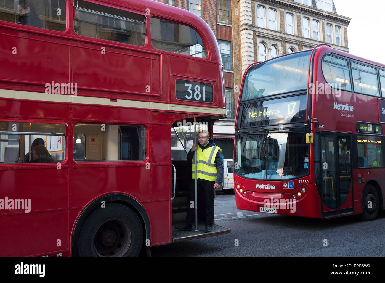 Bus conductor stands on the foot plate of an old red Routemaster bus at London, Bridge, UK. This style of 'hop - Stock Image