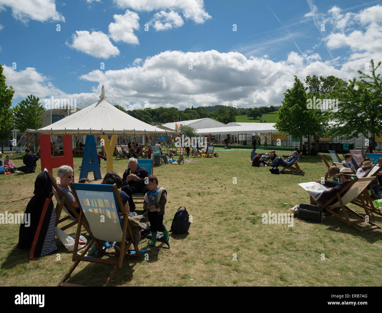 Visitors enjoying and lounging on a sunny Hay Festival 2015 - Stock Image