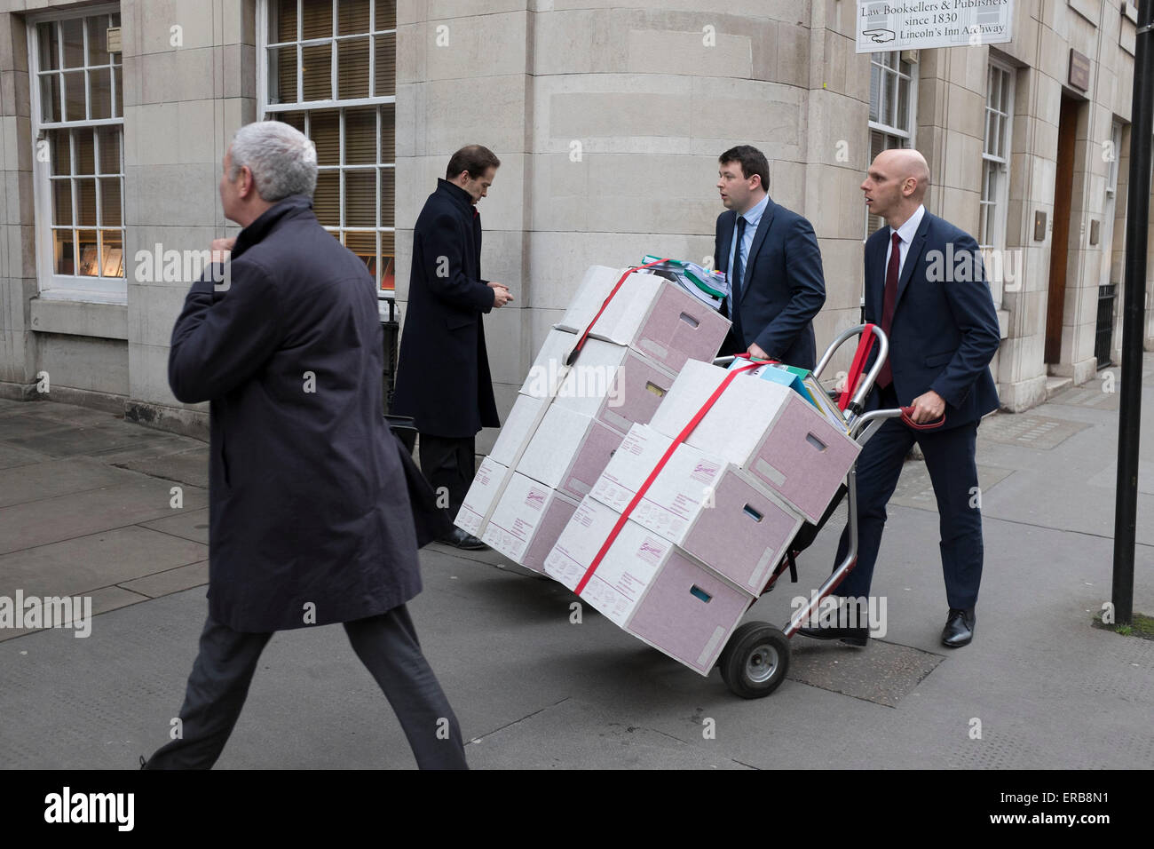 Two men pushing legal papers along Fleet Street towards the Inns of Court in London, UK. - Stock Image