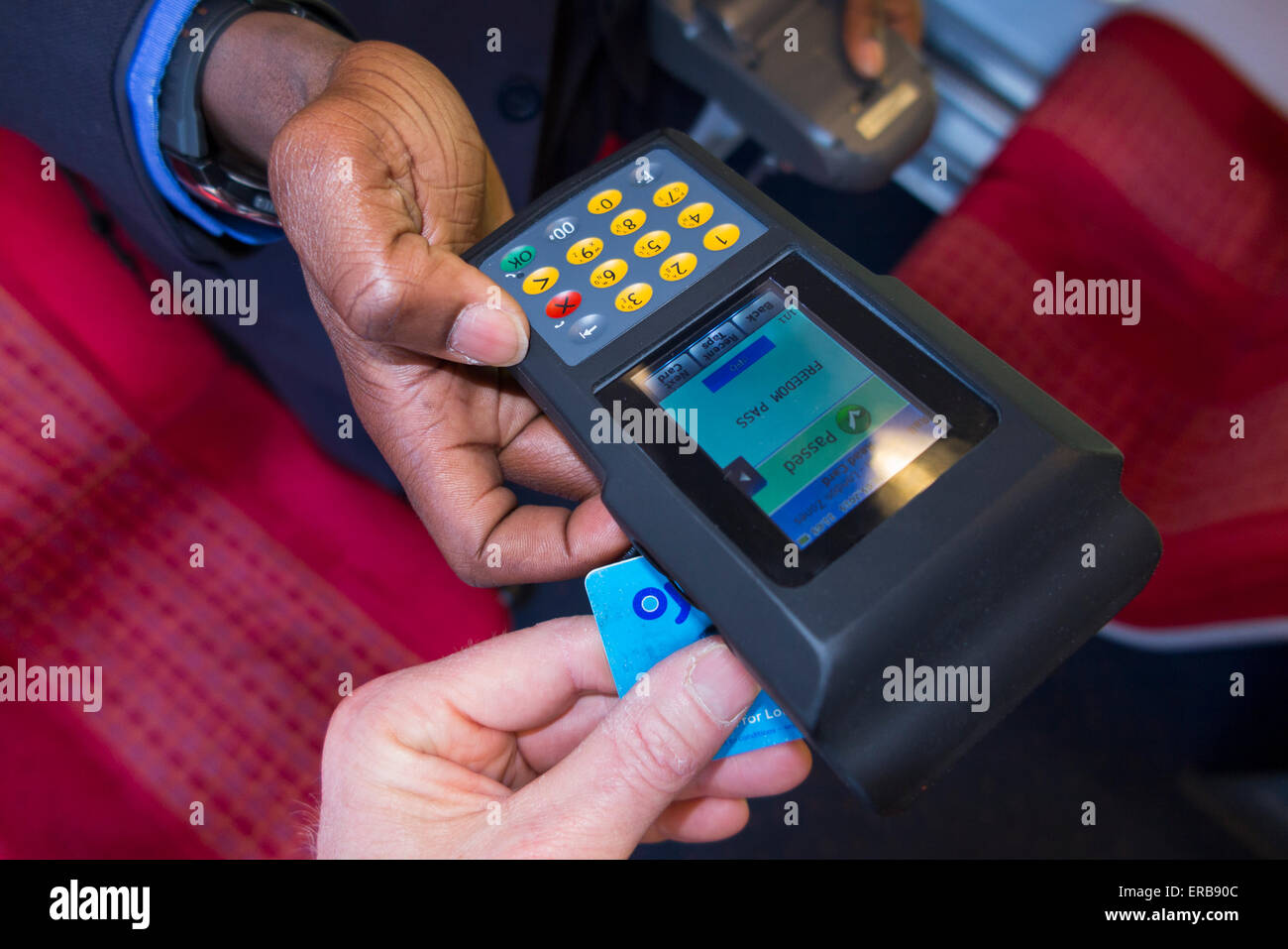 Inspector checks / reads Oyster Card ticket with reader on SW Trains overground train also valid LT bus /underground - Stock Image
