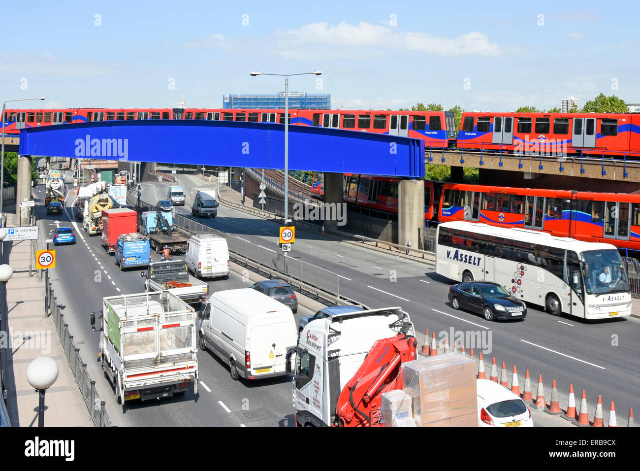 Traffic queuing to enter the Limehouse link road tunnel with DLR train on bridge Poplar East London England UK - Stock Image