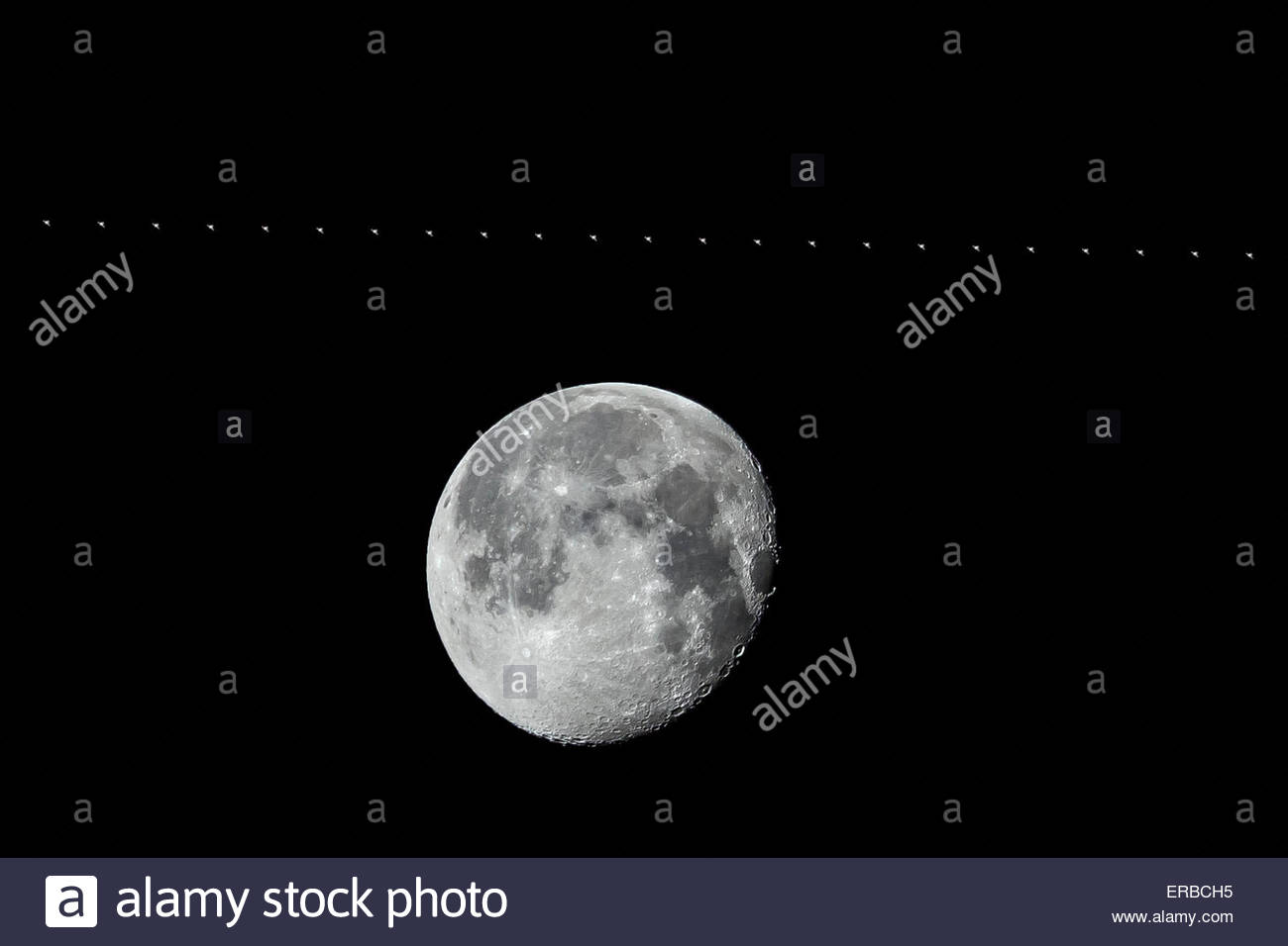 near-full moon waning ISS International Space Station fly-by passing timelapse composite image b/w black & white - Stock Image