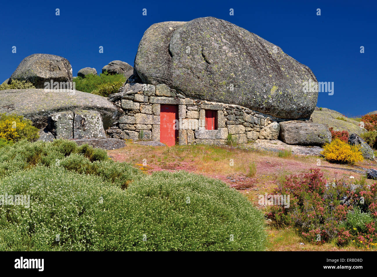 Portugal: Curious stone house under a huge rock in the typical mountain style of the Serra da Estrela - Stock Image