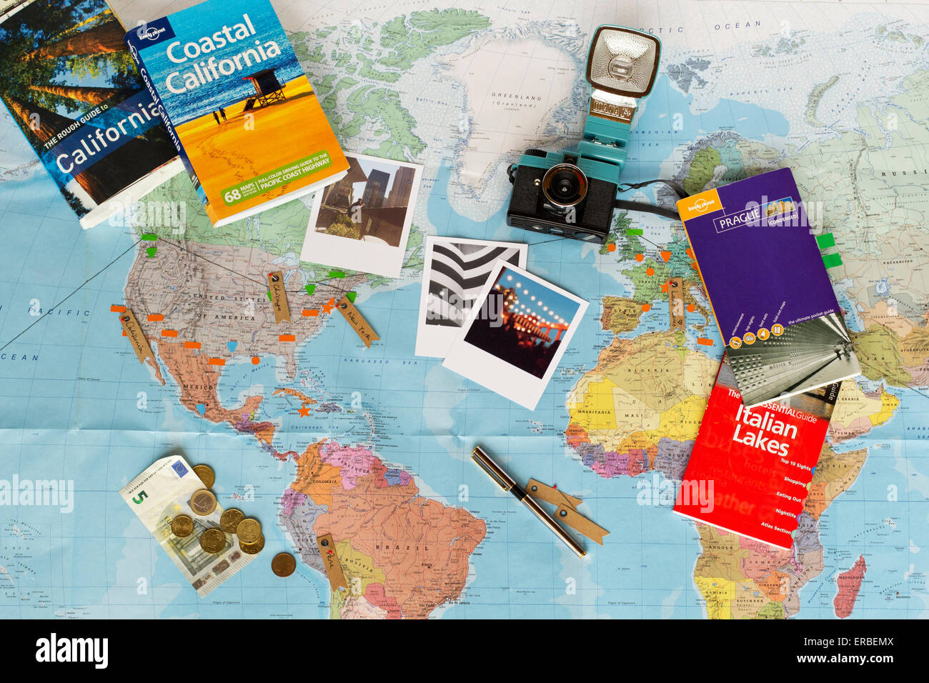 Travel planning. Map of the world, guide books, currency, photographs. - Stock Image